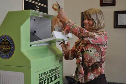 Lori Munkeboe, director of TDEC's Office of Sustainable Practices, demonstrates how to dispose of medications in a bin in Davidson County.