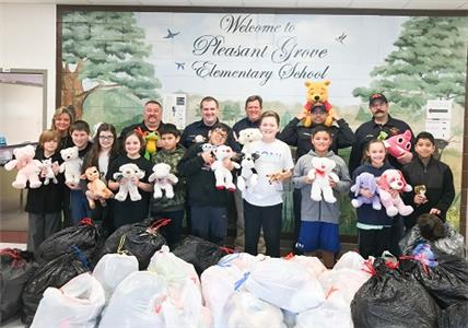 Pictured with some of the students and stuffed animals are (from left, back row) Tammy Whaley of Pleasant Grove, Lt. Garner Hall, Engineer T.J. Floyd, Lt. Chris West, Engineer Ryan Robbs, and Lt. Jamie Franks.
