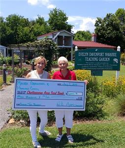 At the Evelyn Davenport Navarre Teaching Garden, Chattanooga Area Food Bank President & CEO Gina Crumbliss (left) receives a donation from Master Gardener and Chairwoman of the 31st Annual Spring Garden Tour Patsy Boles (right) on behalf of the Master Gardeners of Hamilton County