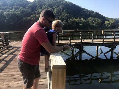 Little girl goes fishing for the first time with her dad from a pier refurbished by union volunteers